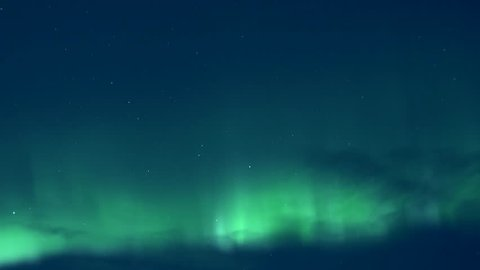 Aurora lights in cold winter, arctic green northern lights. Colour northern lights dancing in dark skies. Burning bright brilliant aurora borealis reflecting ocean breaking, Time lapse clip. Full HD.