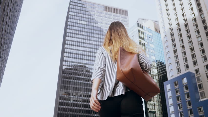 Young beautiful woman walk upstairs to the office in financial district of New York, America. Slow motion.