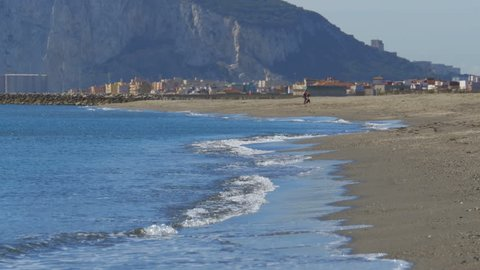 View of the Rock of Gibraltar and the beach with sea waves. Coast of the sea on the border of Gibraltar between Spain and England. Clear blue sky, sunny day in Spain.