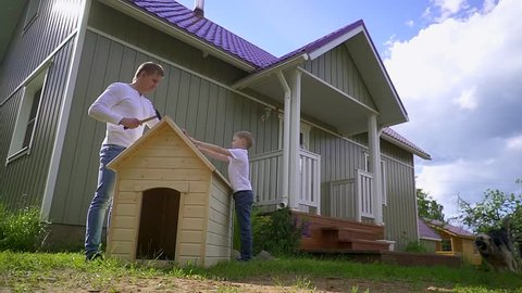 Father and son build a kennel in slow motion
