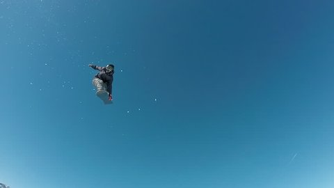 GoPro slow motion - Low angle view of snowboarder flying in the air, jumping over the kicker