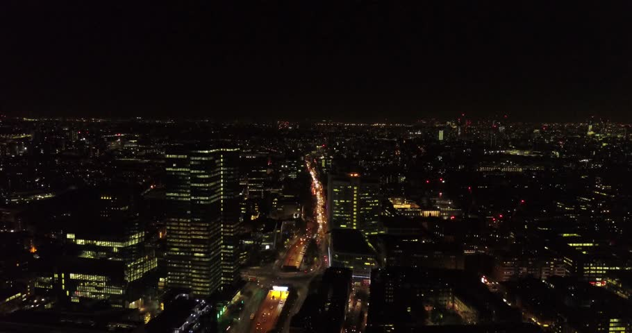 Aerial drone flight above London, uk at night capturing the city lights, landmarks on the Thames and glass office buildings.