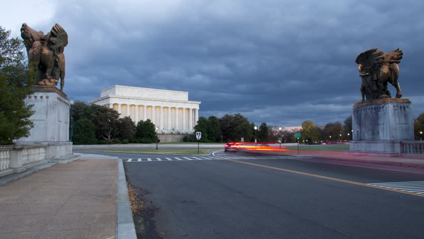 4K time lapse wide shot of long exposure car lights and pedestrians on a street flanked by sculptures approaching the Lincoln Memorial in Washington D.C. at sunset as storm clouds dissipate | Shutterstock HD Video #33235462