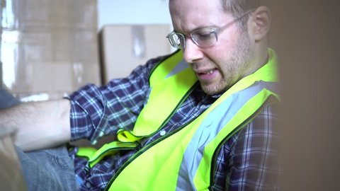 Injury from accident at work. A male warehouse worker man is injured and in pain on floor. For injury compensation claim with lawyer or insurance. A variety of different camera angles available in 4K.