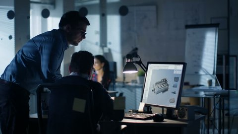 Late at Night Two Industrial Engineers Discuss 3D Component Design Made with CAD Program on Personal Computer. Office Looks Modern with Lots of Blueprints on the Walls. Shot on RED EPIC-W 8K Helium.