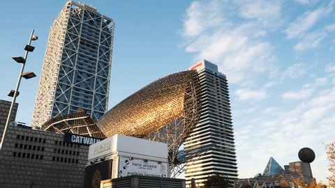 BARCELONA, SPAIN - CIRCA 2017: Calm Barceloneta sandy day with El Peix Frank Gehry's Golden Fish Sculpture built for the 1992 Barcelona Olympics