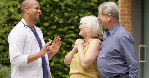 4K Doctor giving good news to overjoyed senior couple outside private hospital