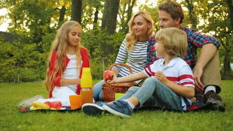 Happy family with kids resting on the grass during a picnic in the picturesque green garden. Sunny weather. Outdoors