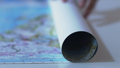 Geographical map unrolled by traveller hand, vacation route planning, closeup