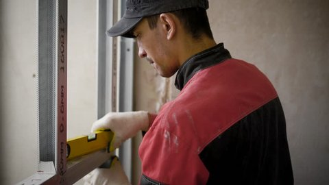 A young worker who works at a construction site works with aluminum profiles, tools for measuring the level, the man delivers repairs in the apartment