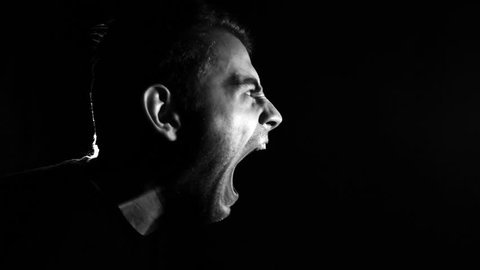 the man screams on a black background in low key, in slow motion, anger emotions