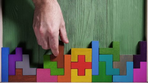 Top view on man's hand playing with colorful wooden blocks on the green wooden table background. The concept of logical thinking.