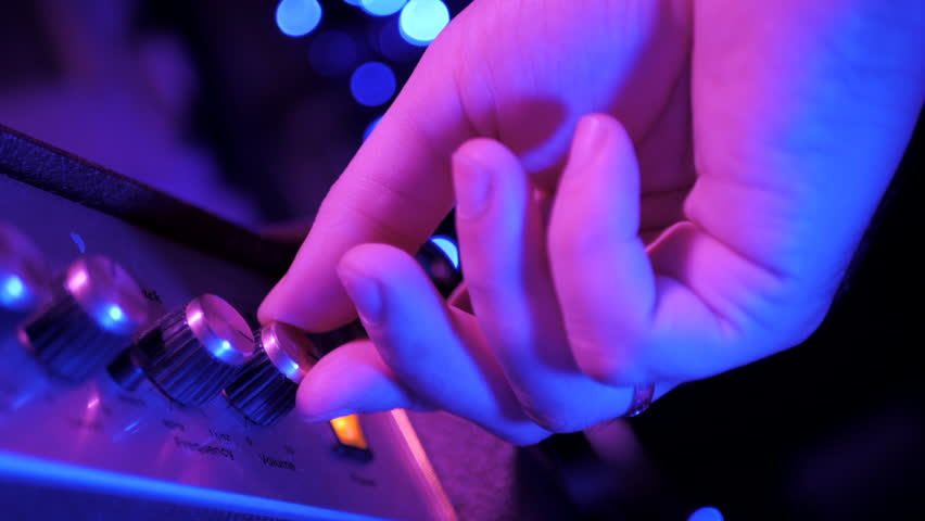 View of the control panel on a guitar amplifier. Tumblers, knobs and buttons. Male hand turn on and increasing music volume on amp. Blue light, Christmas light.