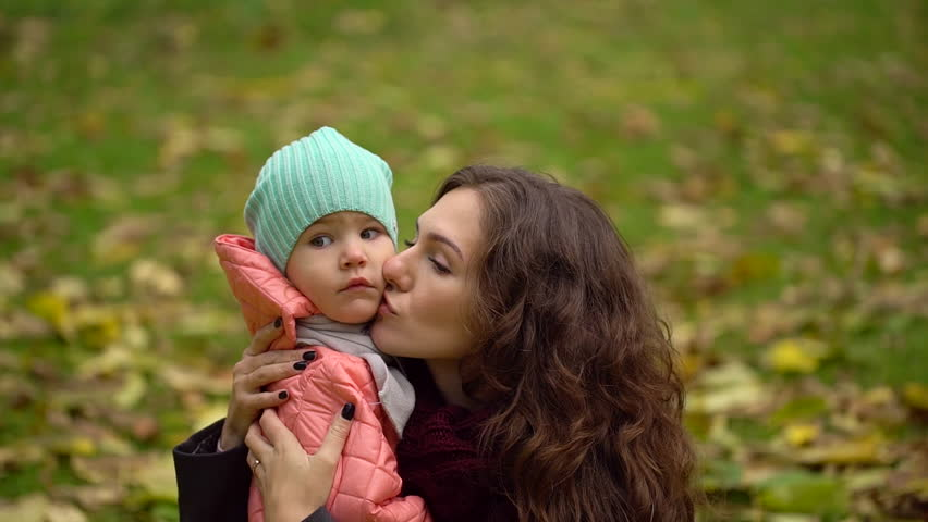 Portrait of beautiful young woman with a child in an autumn park. Portrait of two, young mother and daughter. slow-motion | Shutterstock HD Video #33368242