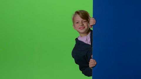 Child boy peeps out from the wall on a green screen