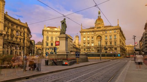 Cordusio Square and Dante street with surrounding palaces, houses and buildings at sunset timelapse in Italian capital of fashion and luxury. Monument to writer and poet Giuseppe Parini. Trams passing