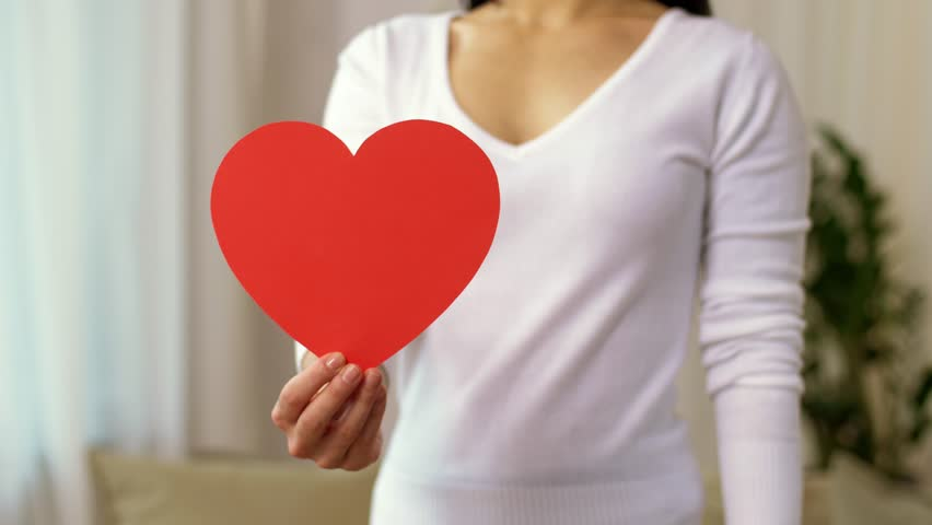 Homosexual and lgbt concept - woman holding red heart shape and wearing gay pride awareness ribbon wristband | Shutterstock HD Video #33387862