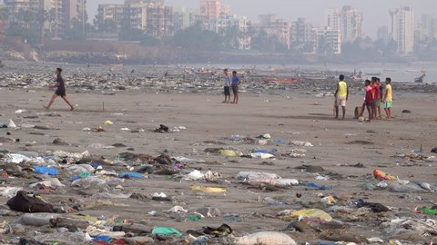 MUMBAI, INDIA - NOV 17: Teenage Indians play game of cricket among plastic garbage and other pollution at Versova Beach on November 17, 2017 in Mumbai, India