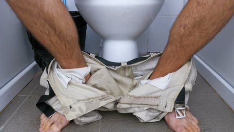 The Legs of a Man Sitting and Stand up from Toilet. A man in shorts and barefoot hairy legs in a white toilet cubicle. Defecation process. Toilet in a public place.