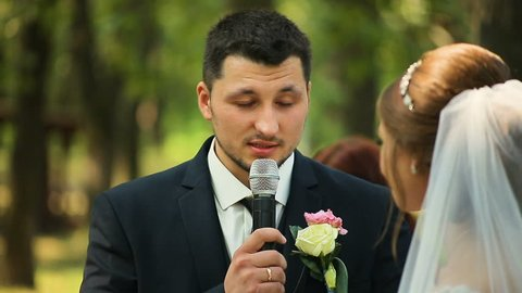 Groom says the oath at wedding ceremony standing in arch decorated