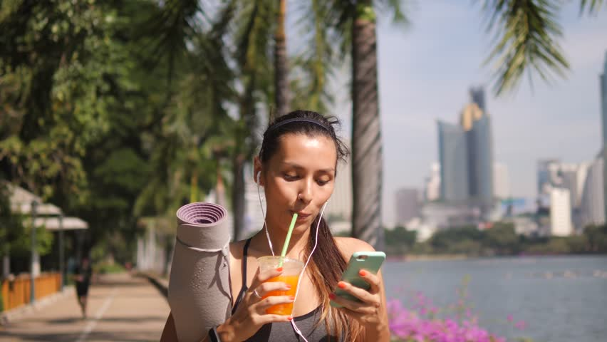 Beautiful Fit Mixed Race Woman Using Mobile Phone App and Drinking Fresh Orange Juice after Morning Yoga Practice in City Park. 4K, Slow Motion. Thailand.