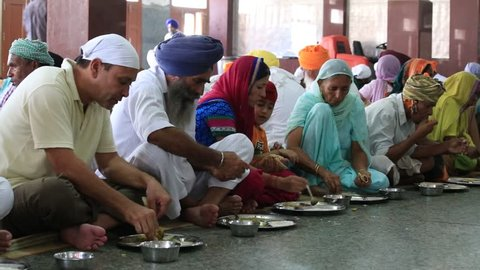AMRITSAR, INDIA - SEPTEMBER 29, 2014: Unidentified poor indian people receive a free meal inside the 'langar', a communal kitchen on the famous Sikh Golden Temple complex in Amritsar.