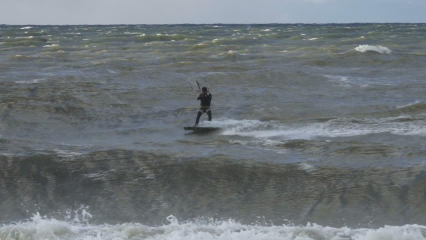 Kiteboarding, Fun in the ocean, Extreme Sport. Extreme Kitesurfing in stormy weather. Summer Ocean Sport in Slow Motion.