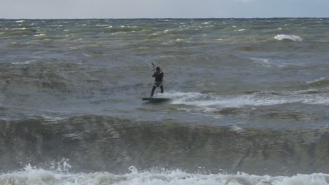 Kiteboarding, Fun in the ocean, Extreme Sport. Extreme Kitesurfing in stormy weather. Summer Ocean Sport in Slow Motion.