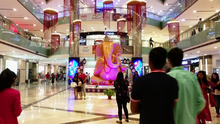 Delhi, India - 28th Oct 2017: Crowd of people shopping in the Ambience shopping mall in Gurgaon. Families clicking photos near the Ganesh Chaturti display during their shopping. Malls like this get