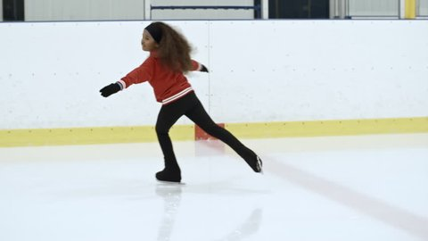Little African girl practicing scratch spins and falling down on ice rink but continuing workout