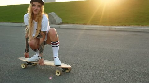 sport, lifestyle, Extreme and people concept - Beautiful girl tattoos riding longboard on the road in the city in sunny weather. Portrait hipster girl smiling with a longboard at sunset. Slow motion