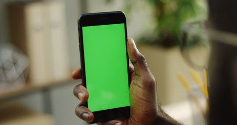 African American male hands holding a blacksmart phone vertically and scrolling on it. Green screen. Chroma key. Blurred room on the background. Close up