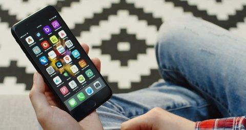 New York - Dec 01, 2017: Male hands holding vertically a black smartphone and using Uber EATS app. Over shoulder. Patterned background. Close up
