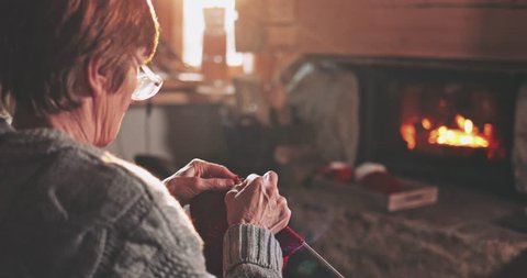 Senior woman hands knitting by the fireplace. Slow motion. Unrecognisable grandmother relaxes by warm fire making handmade gifts for her family. Cozy atmosphere. Winter and Christmas holidays concept.