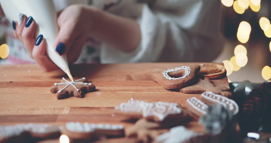 Woman Decorating Baked Gingerbread Christmas Cookies. 4K SLOW MOTION.  Female hands frosting and icing fresh holiday bakery. Festive food, family, Christmas and New Year traditions concept. | Shutterstock HD Video #33513022