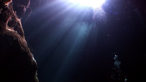Caves of Yucatan cenotes underwater in Mexico. Scuba diving in clean and clear underground water in reflection of sunlight.
