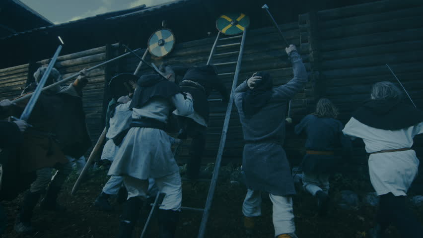 Large-Scale Medieval Battle Reenactment. Violent Tribe of Warriors Attack Wooden Fortress Wall, They Climb Ladders, Guards Try to Defend Fortification.They Fight with Axes, Swords, Spears, Bows.