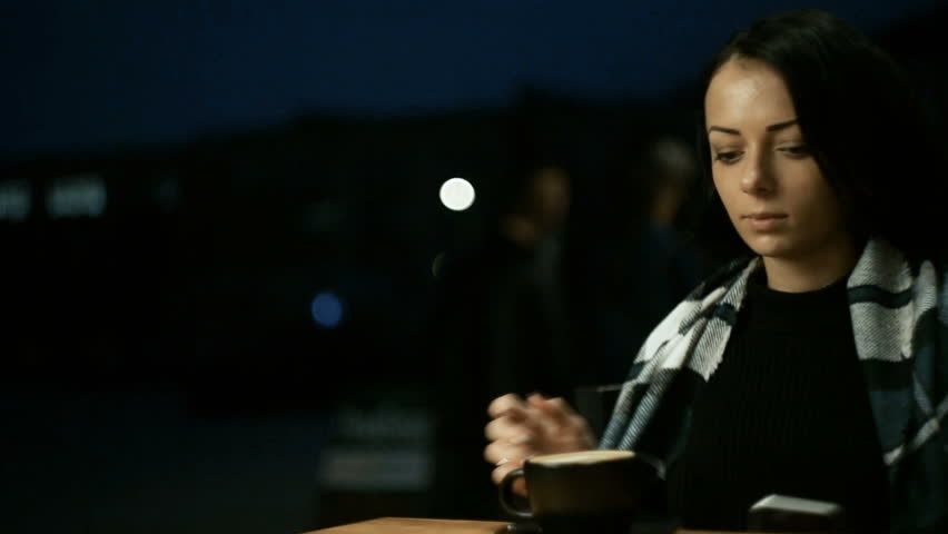 Beautiful young woman sitting in cafe outdoors, in autumn. Wrapped in a blanket. The waiter brings coffee and puts it on the table. | Shutterstock HD Video #33531622