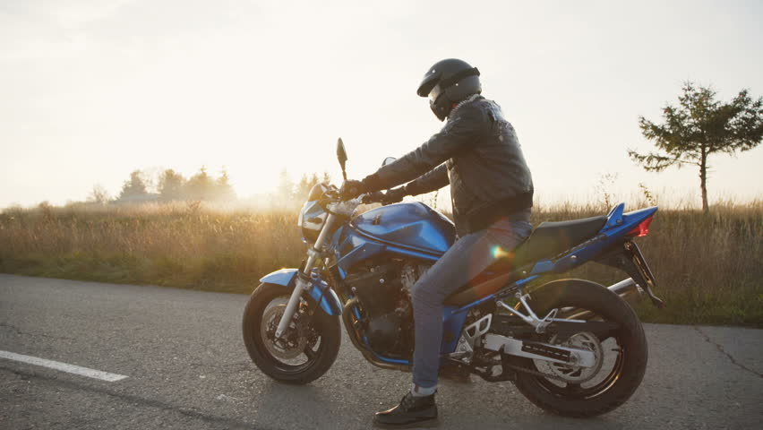 The biker riding on the modern motocycle on the road. 4K.