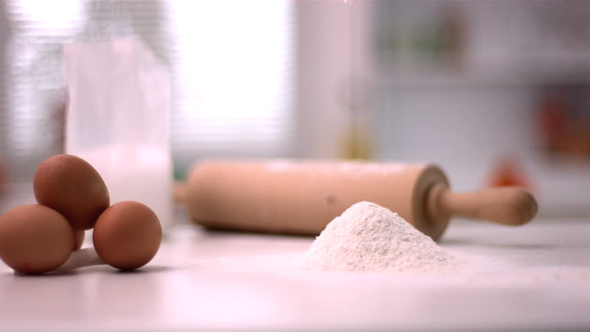 Flour sprinkling on kitchen counter with baking tools in slow motion