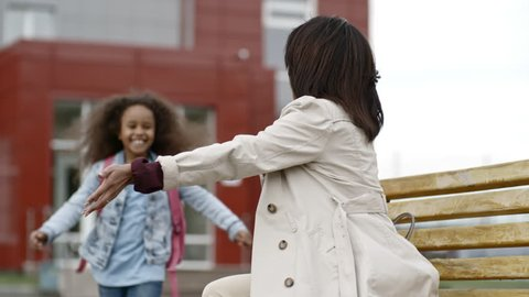 Joyful little girl running to mother, hugging her and giving high five after school