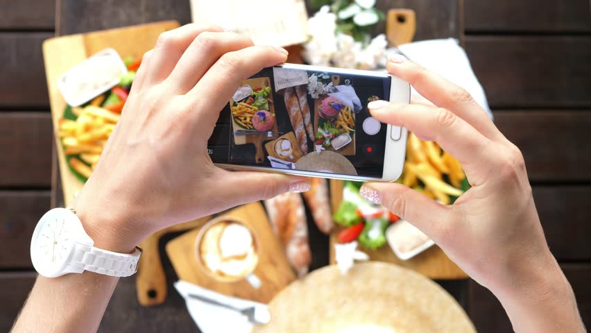 Hands Using Smartphone Taking Photos Of Hipster Flat Lay With Burgers, French Fries, Coffee and French Baguettes. Closeup. 4K.  | Shutterstock HD Video #33583552