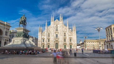 The famous Milan Cathedral timelapse hyperlapse (Duomo di Milano) and monument to Victor Emmanuel II on the Piazza del Duomo in Milan, Italy. Blue cloudy sky at summer day. Milan Duomo is the largest