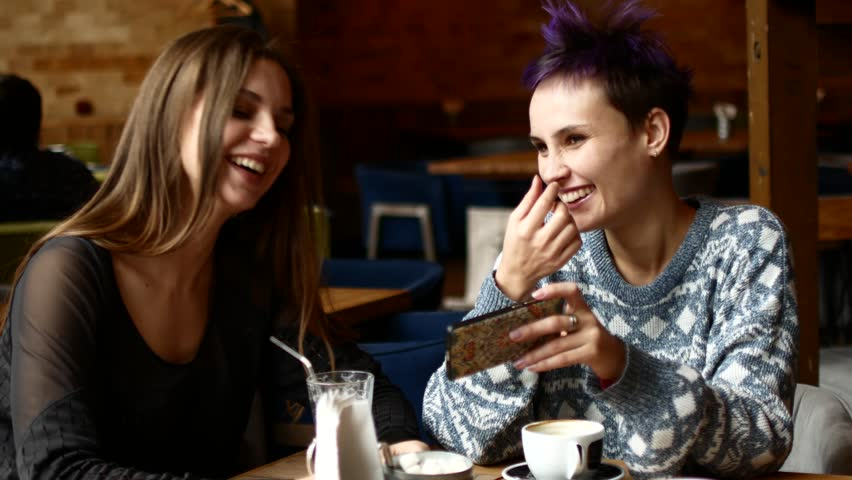 Two friends in a cafe watch video on the smartphone and laugh. Women drink coffee in the coffee house