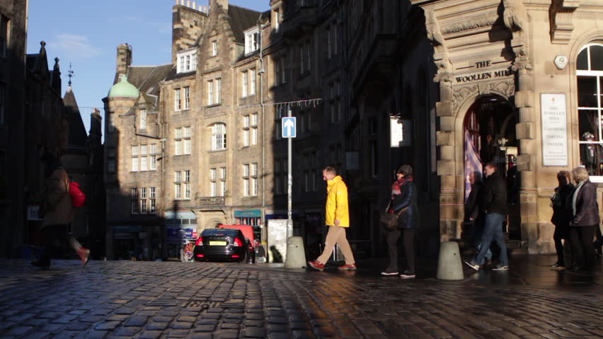 EDINBURGH, UK - 4 DEC, 2017: Tourists walk along the cobbled street of the Royal Mile on a cold but sunny Autumn day