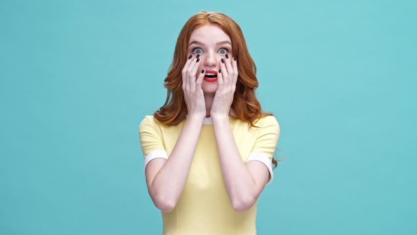 Shocked happy young ginger woman in dress saying omg and looking at the camera over blue background