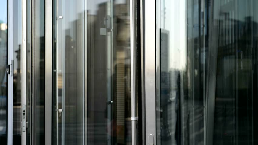 Glass rotating door. Turntable entrance to the business center. Modern buildings and shopping centers & Revolving Door Stock Footage Video | Shutterstock
