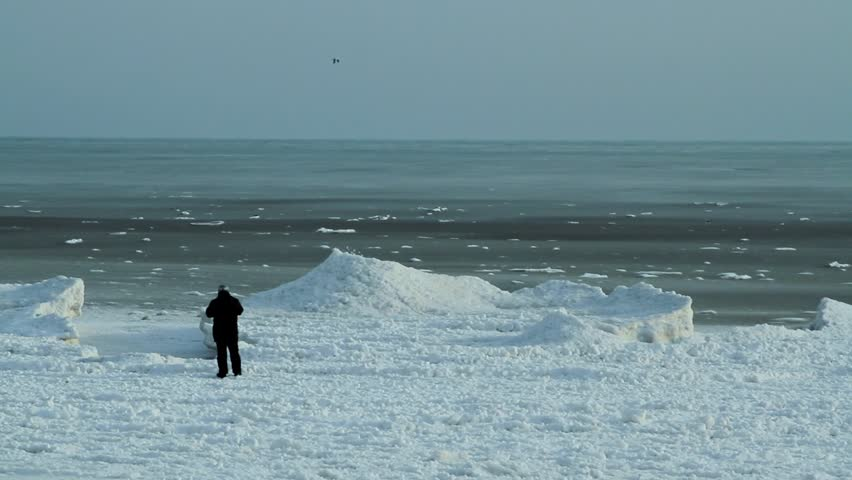 Man looking at the winter sea from the frozen coast. Black sea coast, Bulgaria.