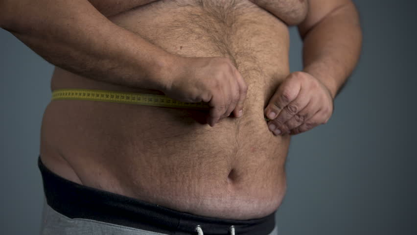 Sad overweight man unable to measure his waist, fat tummy with stretch marks
