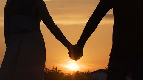 Couple separating their hands at sunset, love story ending, family break-up